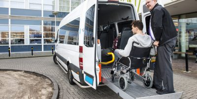 A boy being assisted on a vehicle wheelchair lift